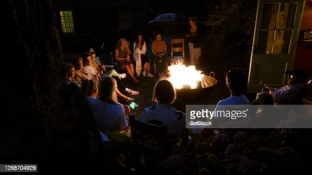 gathering around the fire pit - 20 29 years stock pictures, royalty-free photos & images