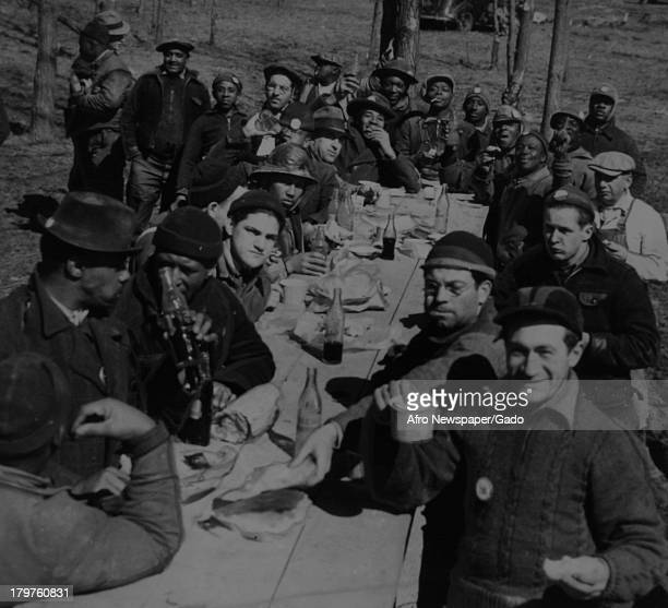 A gathering of men at the Aberdeen Proving Grounds around a picnic table enjoying spirits Aberdeen Maryland March 8 1941