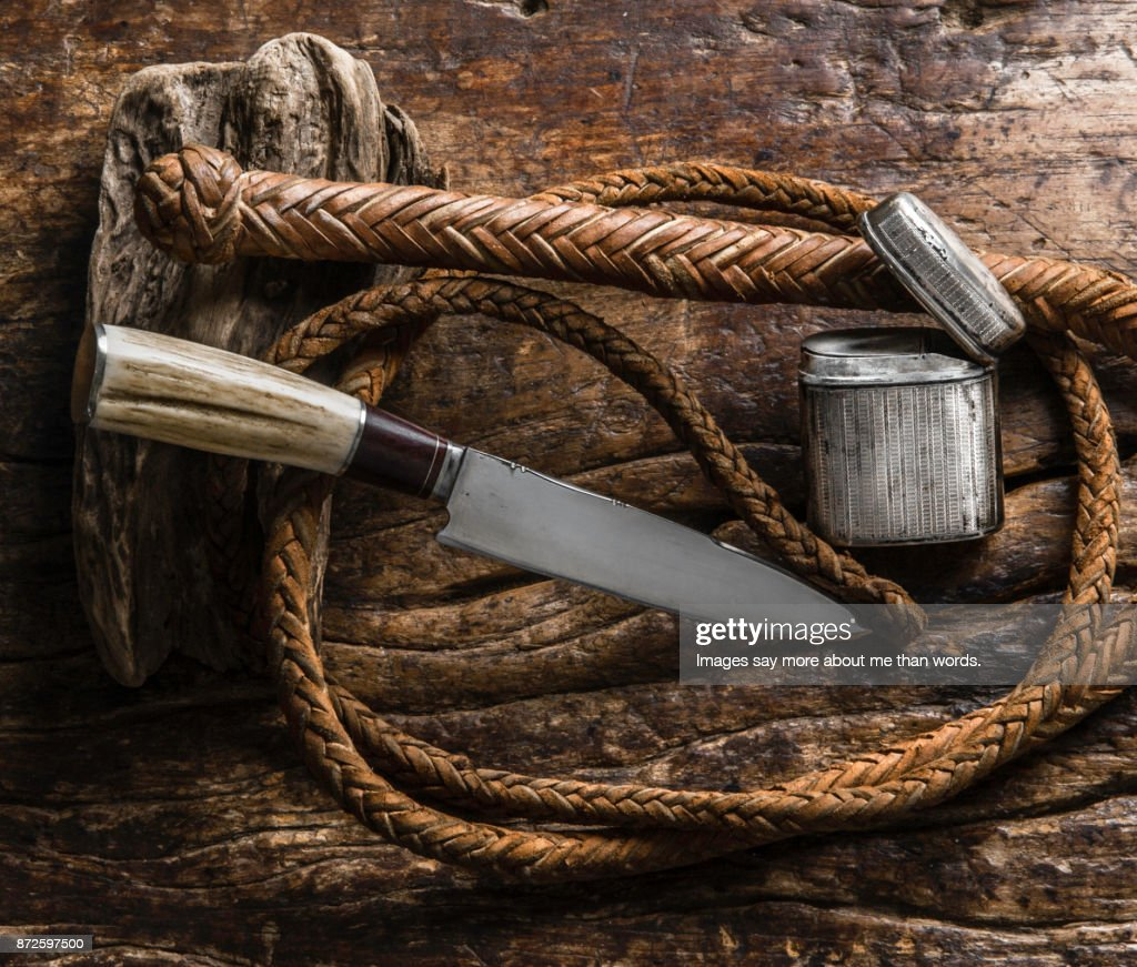 Gaucho knife, whip, silver cigarette case on wood. Still life : Stock Photo