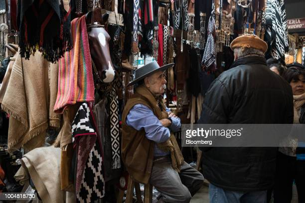 A gaucho sits near fabric goods at the exhibition pavilion during La Exposicion Rural agricultural and livestock show in the Palermo neighborhood of...