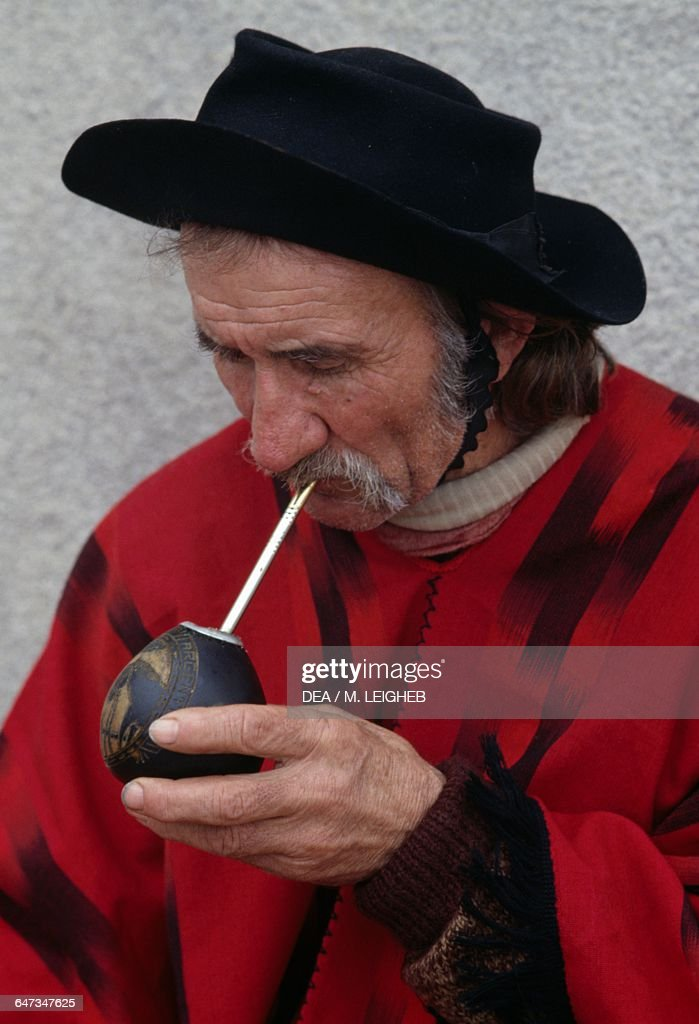 Gaucho wearing hat and poncho drinking mate : News Photo
