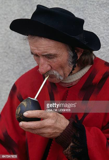 Gaucho wearing a felt hat and poncho drinking mate infusion of yerba mate leaves Argentina