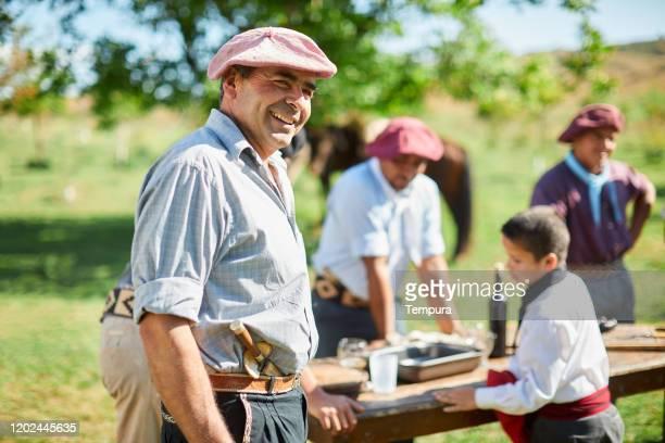 gauchos entspannen und bereiten den tisch für einen asado vor. - argentinischer abstammung stock-fotos und bilder