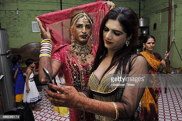 Gaudily dressed eunuchs click selfies during a Bhujariya procession taken out on the third day of Raksha Bandhan on August 31, 2015 in Bhopal, India....