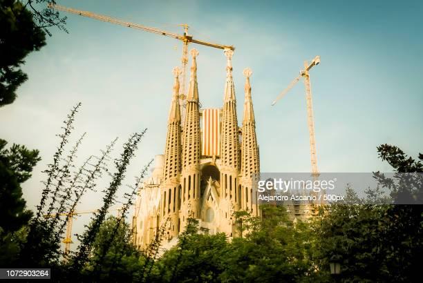gaudi's sagrada familia with catalonia's flag - familia stock pictures, royalty-free photos & images