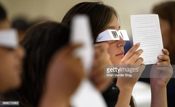 Gault Elementary School fifth grader Angie Rivera right strains to read mock medical forms through plastic glasses which simulate a degenertive eye...