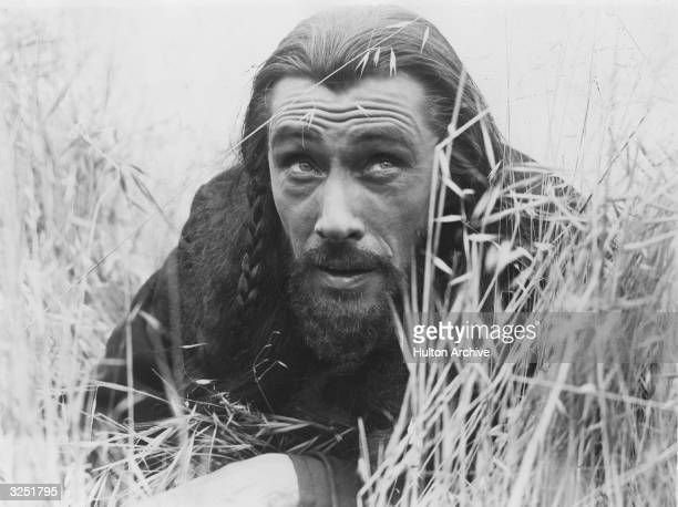 Gaunt American actor John Carradine born Richmond Reed Carradine lying low in the grass in a scene from the film 'Brigham Young' which follows the...