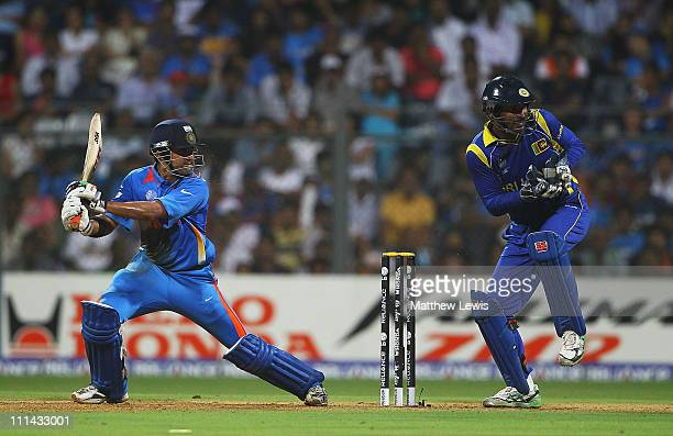 Gautam Gambhir of India hits the ball towards the boundary as Kumar Sangakkara of Sri Lanka looks on during the 2011 ICC World Cup Final between...