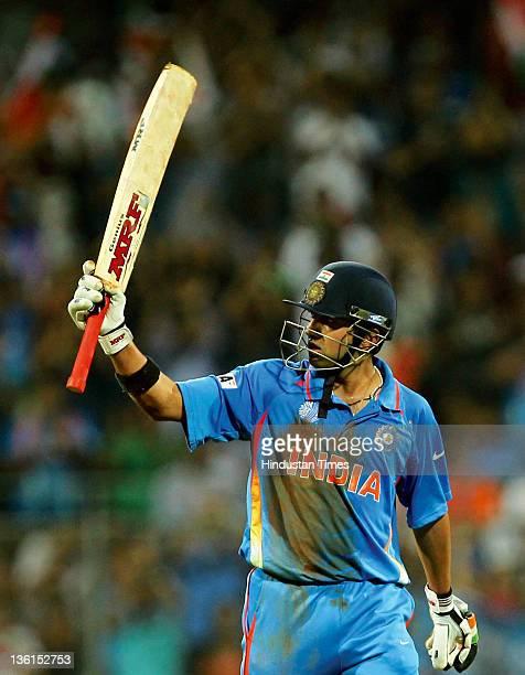 Gautam Gambhir of India raises his bat after scoring a half-century during the 2011 ICC World Cup final between India and Sri Lanka at Wankhede...