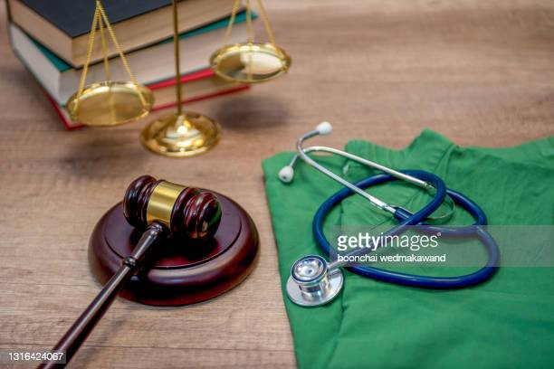 a gavel and a stethoscope on a wooden table concept of medical and legal industries. - legal system stock pictures, royalty-free photos & images