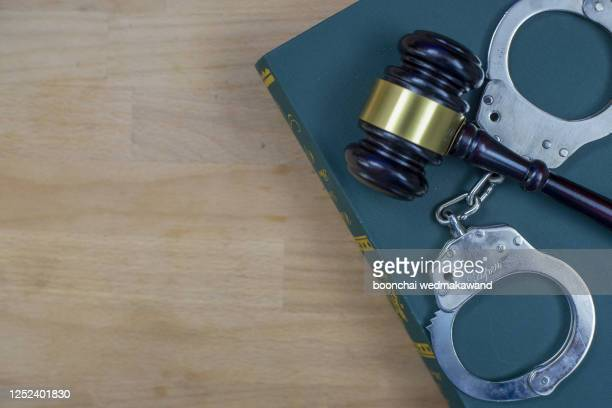 gavel and handcuffs on the law book over the wooden table background - crime or recreational drug or prison or legal trial stock-fotos und bilder