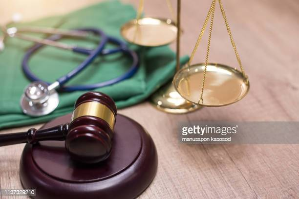 gavel and stethoscope in background. medical laws and legal concept. - medical malpractice stock photos and pictures