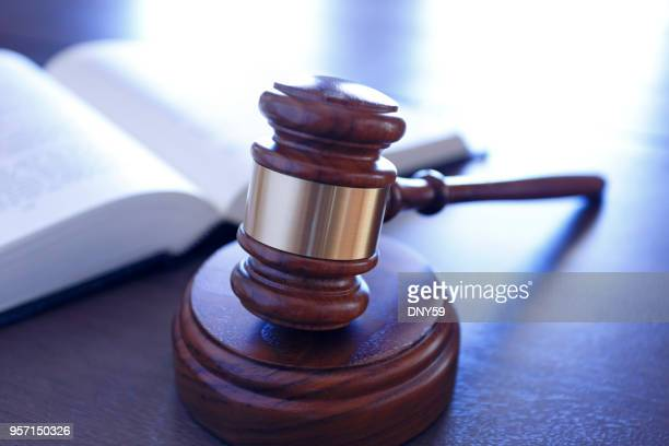 gavel in front of an open law book - lawsuit stock pictures, royalty-free photos & images
