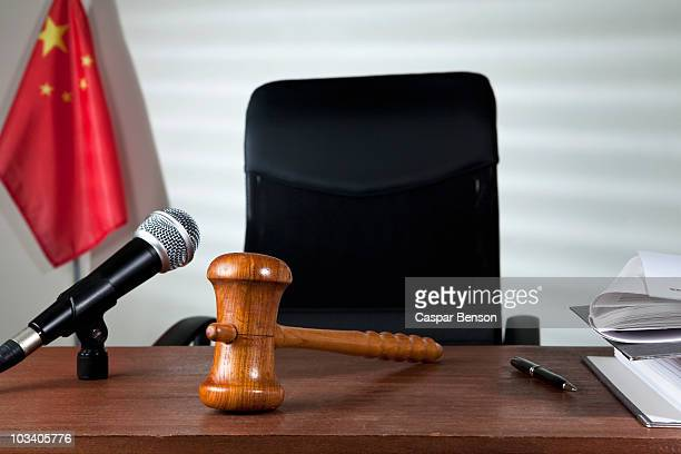 A gavel on a judge's desk in an empty courtroom