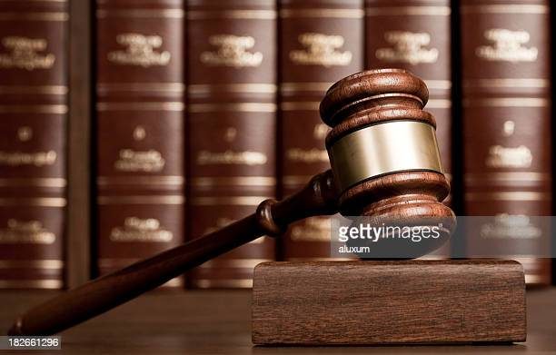Gavel on wooden desk with books as background