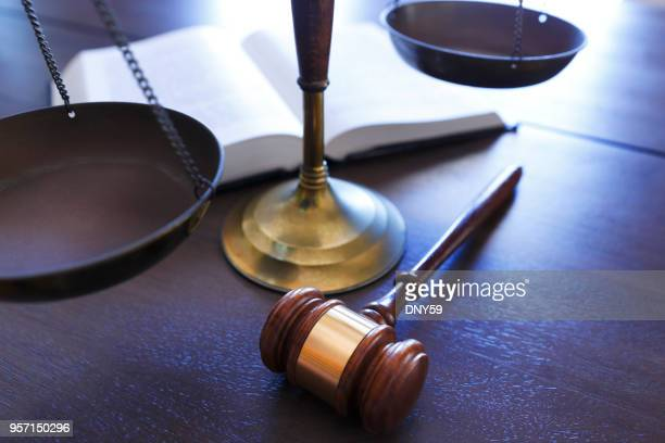 gavel rests in front of justice scale and open law book - equal arm balance stock pictures, royalty-free photos & images