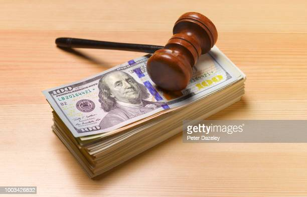 gavel sitting on pile of dollar notes - corruption stock pictures, royalty-free photos & images
