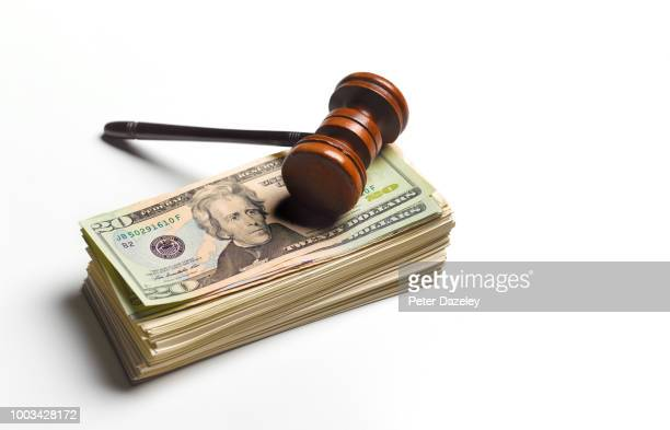 gavel sitting on pile of dollars - lawsuit stock pictures, royalty-free photos & images