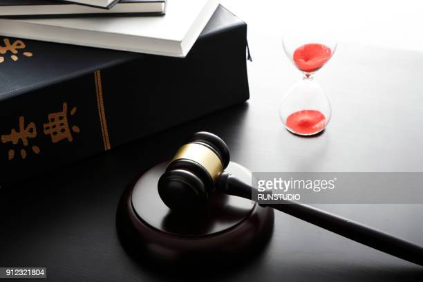Gavel with stacked law books and hour glass