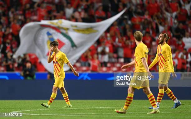 Gavi, Frenkie de Jong and Oscar Mingueza walk off the field dejected after the UEFA Champions League group E match between SL Benfica and FC...