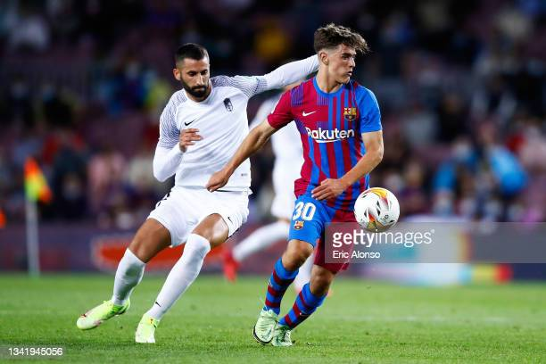 Gavi Paez of FC Barcelona competes for the ball with Maxime Gonalons of Granada CF during the La Liga Santander match between FC Barcelona and...