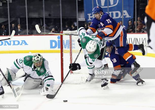 Gavin Bayreuther of the Dallas Stars is checked by Cal Clutterbuck of the New York Islanders during the second period at the Barclays Center on...
