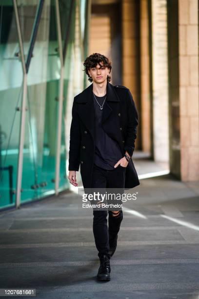 Gavin Casalegno wears a black long coat, a t-shirt, a necklace, black ripped jeans, black shoes, outside Vivetta, during Milan Fashion Week...