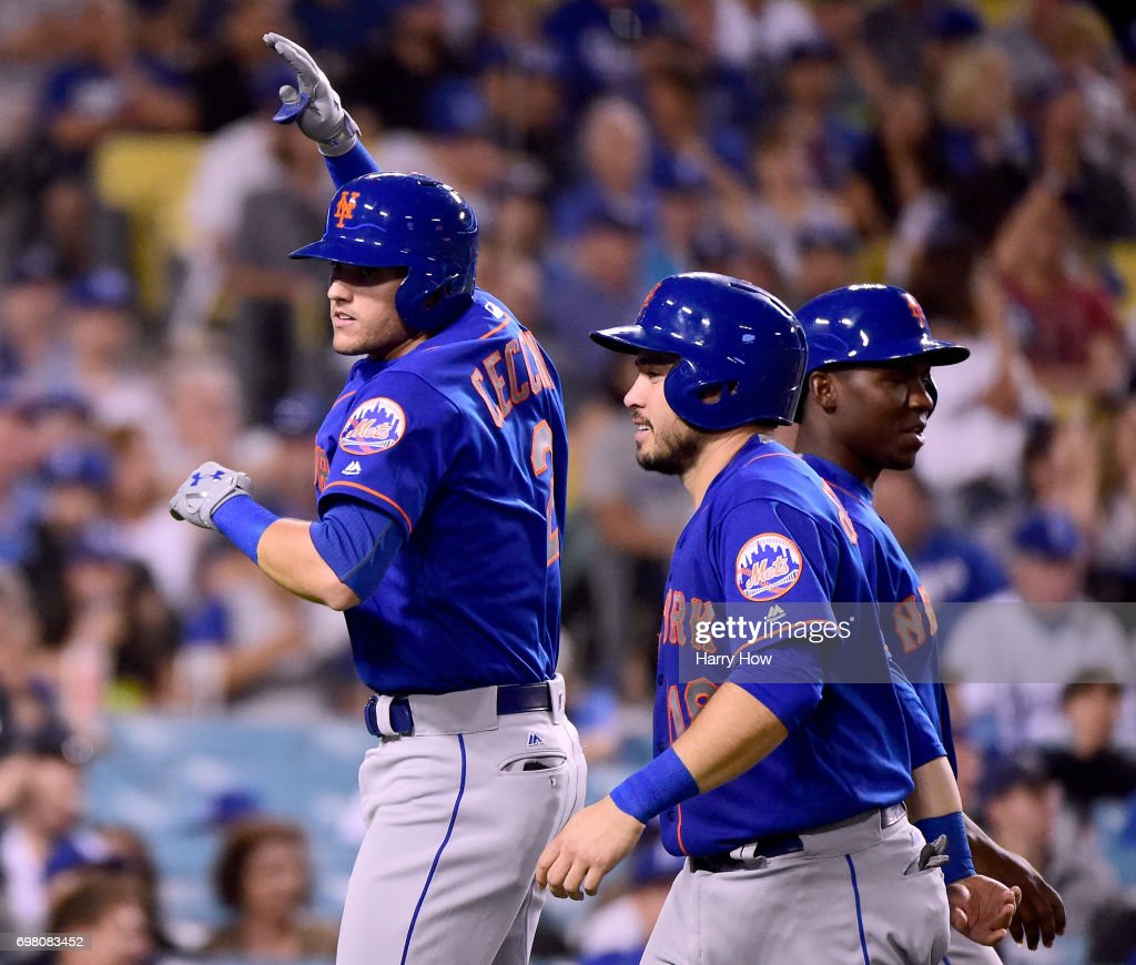 Gavin Cecchini #2 of the New York Mets celebrates his two run homerun with Travis d'Arnaud #18 and T.J. Rivera #54 to trail 7-4 to the Los Angeles Dodgers during the fifth inning at Dodger Stadium on June 19, 2017 in Los Angeles, California.