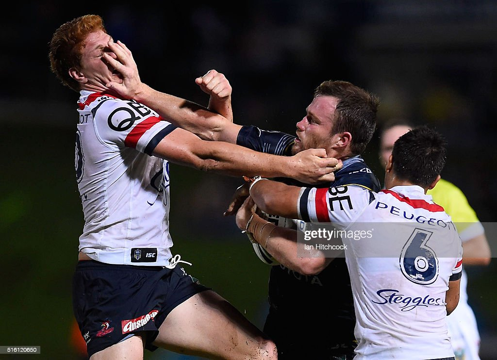 Gavin Cooper of the Cowboys fends Dylan Napa of the Roosters during the round three NRL match between the North Queensland Cowboys and the Sydney Roosters at 1300SMILES Stadium on March 17, 2016 in Townsville, Australia.