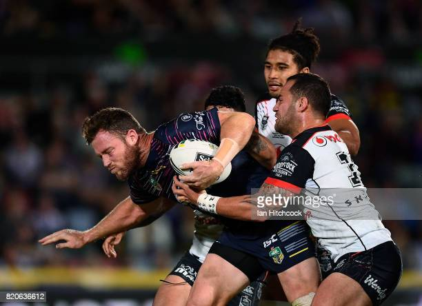 Gavin Cooper of the Cowboys is tackled by Bodene Thompson and Issac Luke of the Warriors during the round 20 NRL match between the North Queensland...