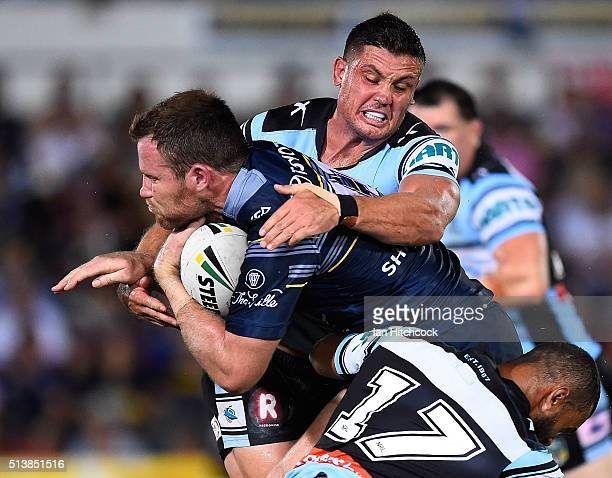 Gavin Cooper of the Cowboys is tackled by Chris Heighington and Jayson Bukuya of the Sharks during the round one NRL match between the North...