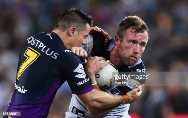 Gavin Cooper of the Cowboys is tackled by Cooper Cronk of the Storm during the 2017 NRL Grand Final match between the Melbourne Storm and the North...