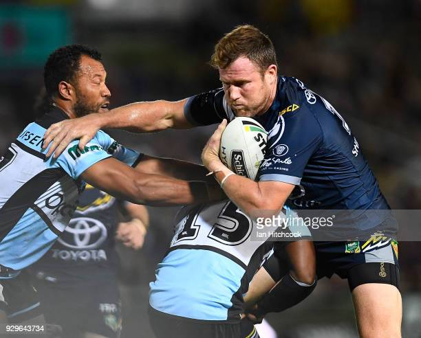 Gavin Cooper of the Cowboys is tackled by James Segeyaro of the Sharks during the round one NRL match between the North Queensland Cowboys and the...