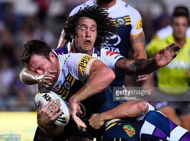 Gavin Cooper of the Cowboys is tackled by Kevin Proctor of the Storm during the round four NRL match between the North Queensland Cowboys and the...