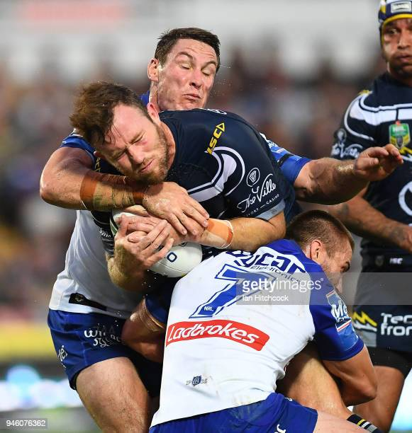 Gavin Cooper of the Cowboys is tackled by Kieran Foran and Josh Jackson of the Bulldogs during the round six NRL match between the North Queensland...