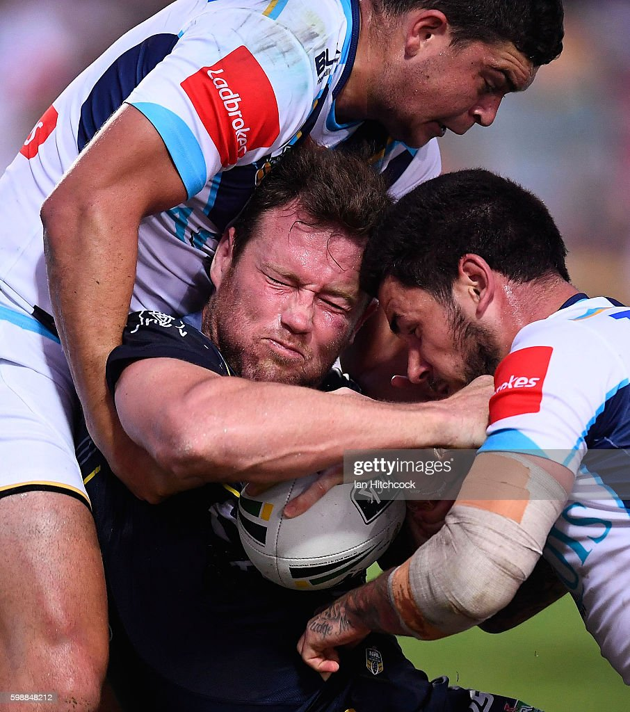Gavin Cooper of the Cowboys is tackled by Nathan Peats and Ashley Taylor of the Titans during the round 26 NRL match between the North Queensland Cowboys and the Gold Coast Titans at 1300SMILES Stadium on September 3, 2016 in Townsville, Australia.