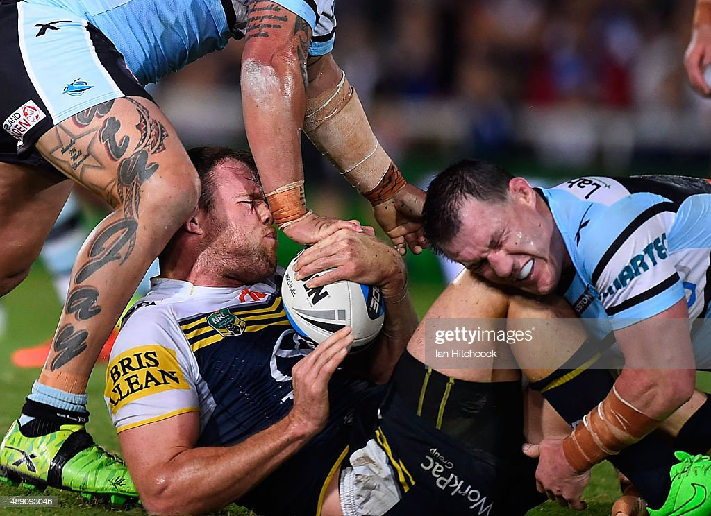 Gavin Cooper of the Cowboys is tackled by Paul Gallen and Andrew Fifita of the Sharks during the Second NRL Semi Final match between the North Queensland Cowboys and the Cronulla Sharks at 1300SMILES Stadium on September 19, 2015 in Townsville, Australia.