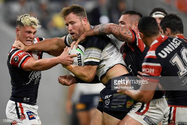 Gavin Cooper of the Cowboys is tackled during the round nine NRL match between the North Queensland Cowboys and the Sydney Roosters at QCB Stadium on...