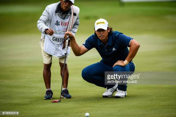 Gavin Green of Malaysia and his caddie look at the green during round two of the Hong Kong Open at the Hong Kong Golf Club on November 24 2017 / AFP...