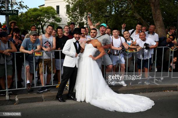 Gavin Haughain and partner Aiden Eric pose as onlookers cheer during the 2020 Sydney Gay Lesbian Mardi Gras Parade on February 29 2020 in Sydney...