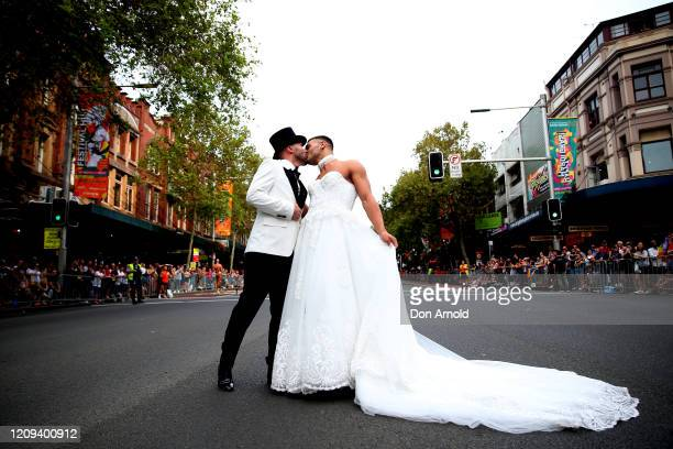 Gavin Haughain and partner Aiden Eric share a kiss as onlookers cheer during the 2020 Sydney Gay Lesbian Mardi Gras Parade on February 29 2020 in...