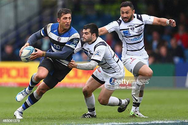 Gavin Henson of Bath looks for support as Thomas Laranjeira of Brive challenges during the Amlin Challenge Cup QuarterFinal match between Bath and...