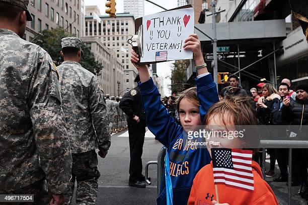 Gavin Kinney left and his brother Rigel hold up a sign thanking veterans at the nation's largest Veterans Day Parade in New York City on November 11...