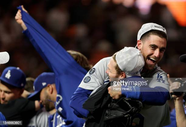 Gavin Lux holds up Cody Bellinger of the Los Angeles Dodgers as they celebrate their 2-1 win against the San Francisco Giants in game 5 of the...