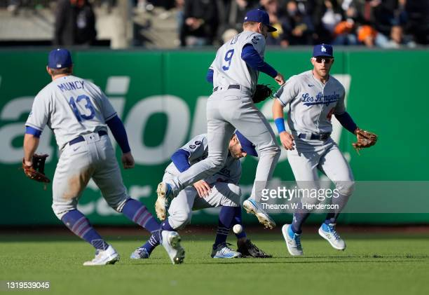 Gavin Lux of the Los Angeles Dodgers leaps over the ball to avoid colliding with teammate Chris Taylor on a single off the bat of Evan Longoria of...