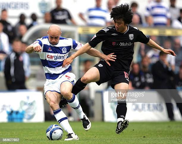 Gavin Mahon of QPR and Kim DoHeon of West Bromwich Albion in action during the CocaCola League Championship match between Queens Park Rangers and...