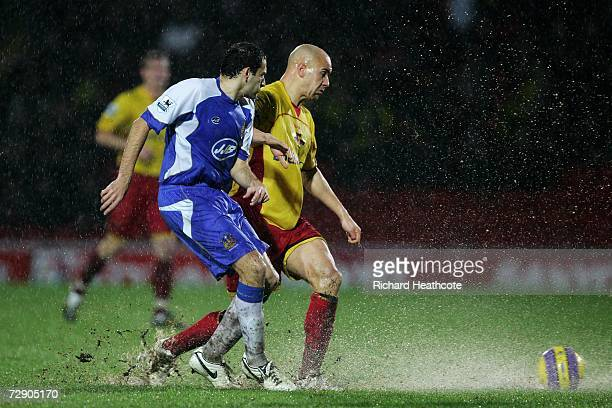 Gavin Mahon of Watford and Josip Skoko of Wigan battle for the ball in the heavy rain during the Barclays Premiership match between Watford and Wigan...