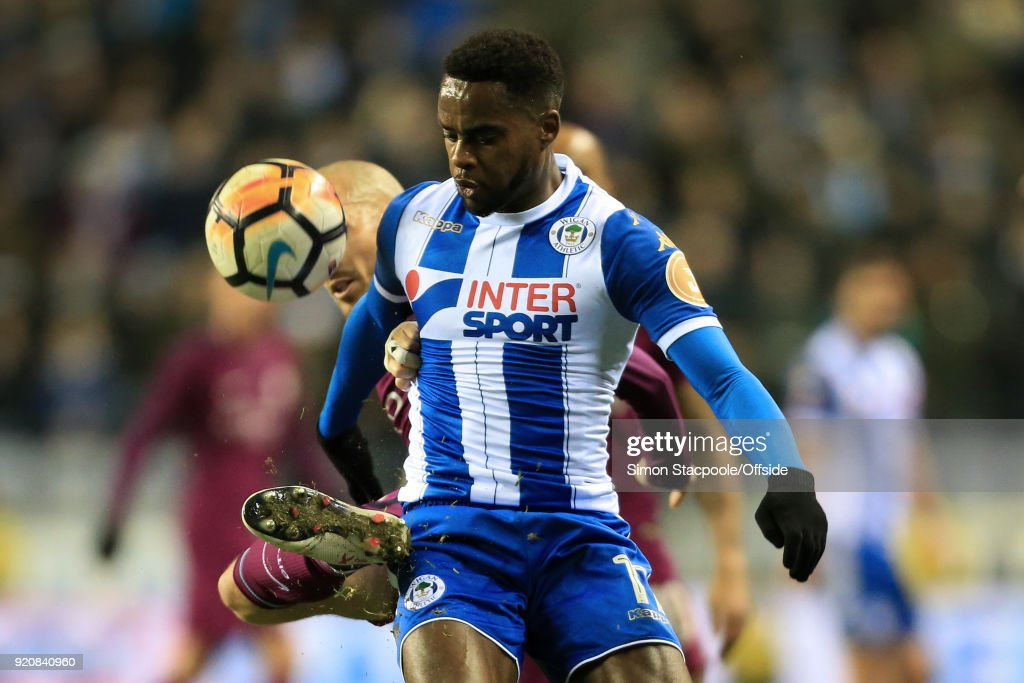Gavin Massey of Wigan battles with David Silva of Man City during The Emirates FA Cup Fifth Round match between Wigan Athletic and Manchester City at the DW Stadium on February 19, 2018 in Wigan, England.
