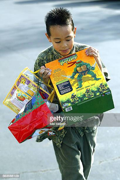 Gavin Molenhouse takes a look at his new toy a teenage mutant ninja turtle that he was given during a Christmas party for the children of striking...