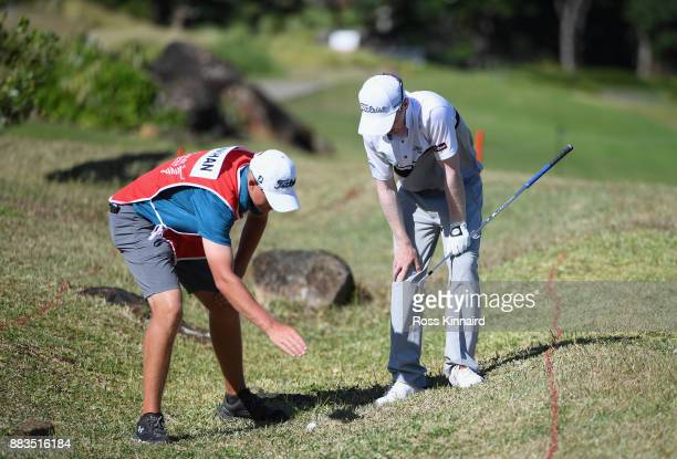 Gavin Moynihan of Ireland and his caddie inspect the lie of the ball during day two of the AfrAsia Bank Mauritius Open at Heritage Golf Club on...